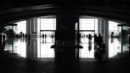 View of entrance to railway station with silhouettes of people with suitcases
