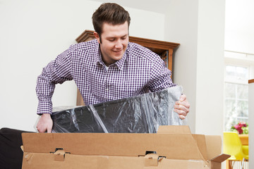 Man Unpacking New Television At Home