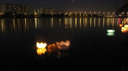 Multi-colored water small lamps float down river in evening
