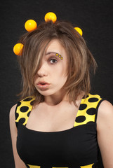 Studio portrait of funny young women with yellow balls in hair