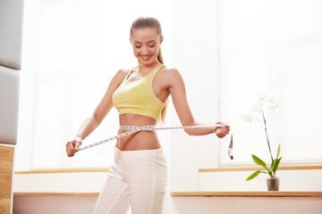 Diet.  Woman in Sportswear Measuring Her Waist