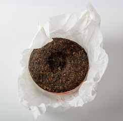 chinese puer tea cake in unwrapped packing on white background