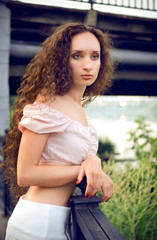 Outdoor portrait of young woman near brige