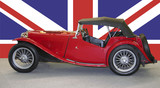 old red britsh car with british flag
