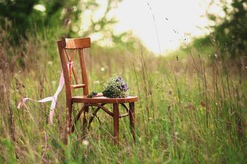 Красивый деревянный стул на природе с букетом