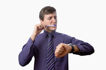 Young man brushing his teeth also looks on at watch