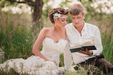 Красивая молодая пара читает книгу на природе