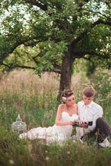 Жених и невеста отдыхают на природе и читают книгу