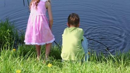 Two kids sit near pond and play with fishing rods