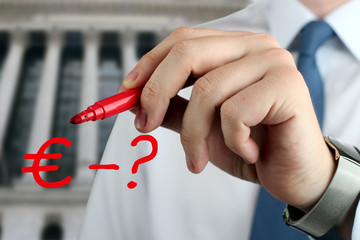 Man drawing a sign of  euro with question by red pen