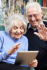 Senior Couple Using Digital Tablet For Video Call With Family
