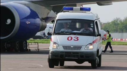 ambulance leaves from under the wing of an airplane