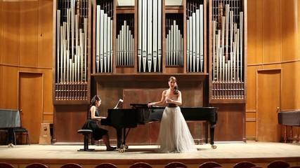 Woman pianist plays piano and singer sing opera song at stage