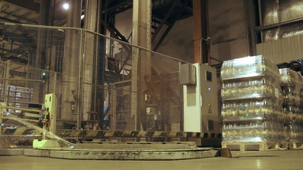 Special machine wrap up by overwrap of container with kvass bottles at nonalcoholic plant, time lapse