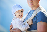 Happy toddler boy in sling, father carrying son outdoors