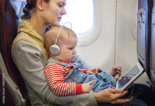 mother and toddler son using tablet pc while on board - 80154684