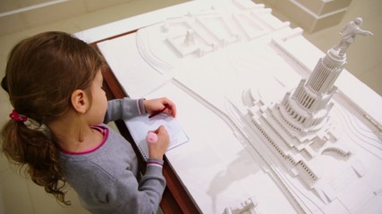 Little girl draws near miniature of project of Palace of Soviets