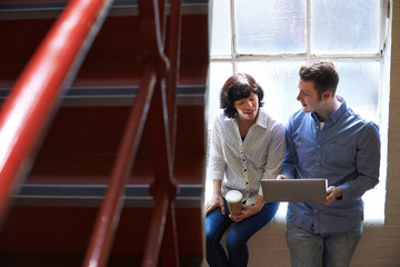 Two Businesspeople Having Informal Meeting On Office Stairs