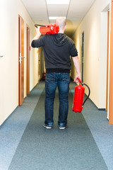 man holding two fire extinguishers