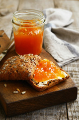 Butter and apricot jam sandwich sunflower seeds on cutting board