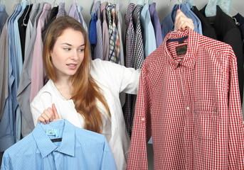 Mitarbeiterin einer Textilreinigung mit zwei schmutzigen Hemden