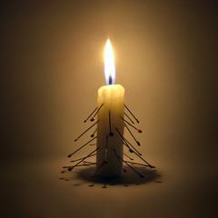 Burning candle larded with needles