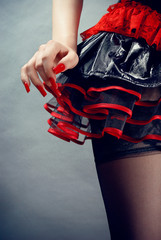 Female in black and red fetish skirt on blue background