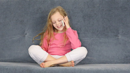 Blonde girl talks to mobile phone and sits on grey sofa