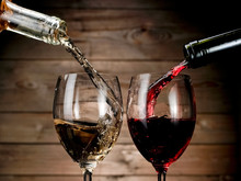 "Постер, картина, фотообои ""Red and white wine pouring on wood background"""