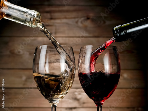Plexiglas Wijn Red and white wine pouring on wood background