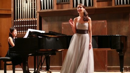 Graceful woman pianist and opera singer finishes the performance