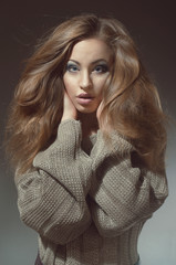 Young woman with beautiful long hair  in knitted  gray sweater