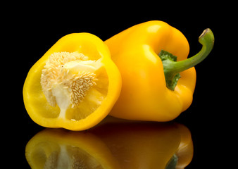 Closeup halved yellow bell peppers isolated on black