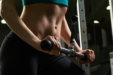 Close up of a girl working out on a cable machine in the gym