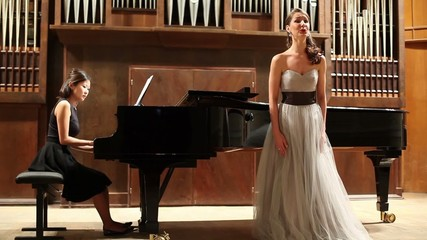 woman pianist and opera singer finishes the performance