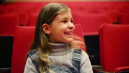 girl sits on red chair and smiles in empty auditorium of theater