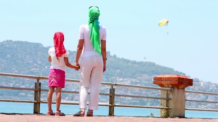 Mother and daughter stand holding hands looking at parasail