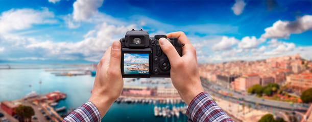 DSLR camera in hand shooting cityscape panorama