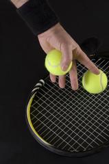 Human Hand Grabbing Green Tennis Ball on Black Bakground