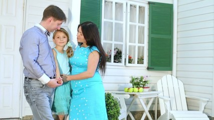Happy family stands next to porch of new white house.