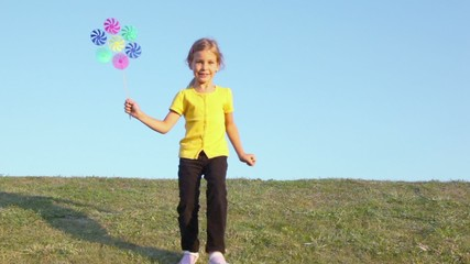 Little girl holds windmill toy and runs from behind of grass hill
