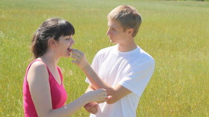 guy and girl feed each other with wild strawberry in field