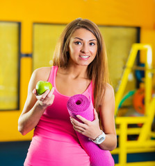 Beautiful woman with a yoga mat and green apple at the gym