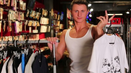 Muscular smiling man in a vest chooses clothes at shop