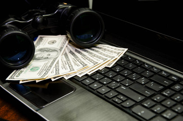 a lot of money on a laptop keyboard with binoculars