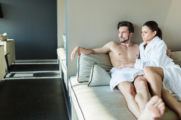 Couple relaxing at a wellness center, laying in a rob and towel