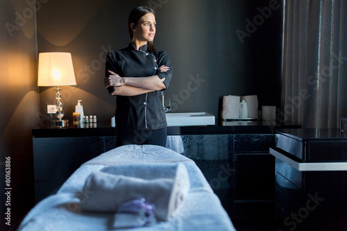 Massage therapist standing by massage table with hands crossed - 80163886