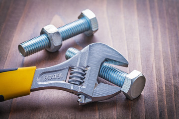 adjustable wrench and bolts on vintage wooden board construction