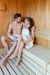 Young and beautiful couple relaxing and hugging in a sauna