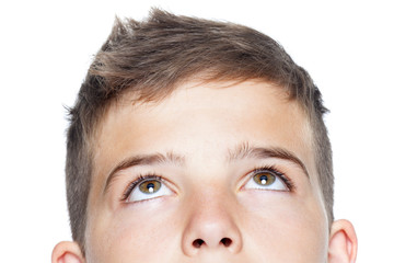 Closeup of teenager boy looking up, isolated on white